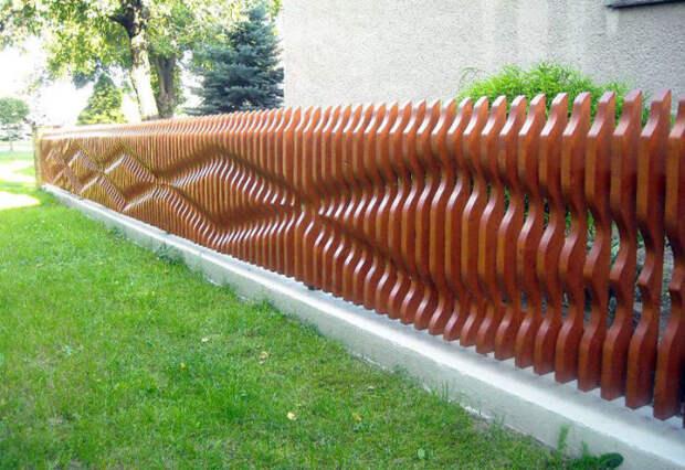 Забор из фигурных планок смотрится эффектно. /Фото: cs6.livemaster.ru