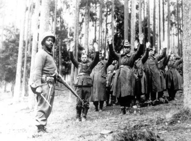 Американский солдат из 12-й бронетанковой дивизии рядом с группой пленных солдат.