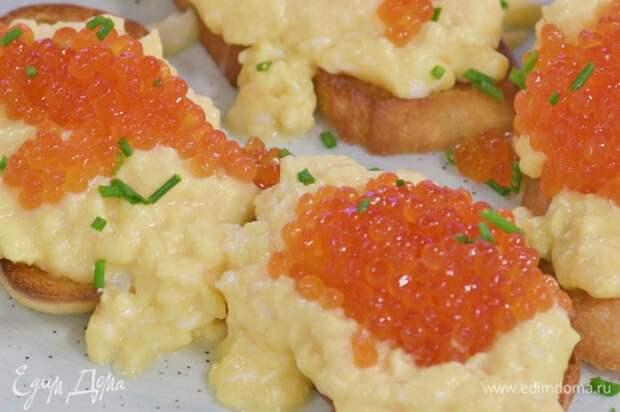 На тосты выложить взбитый омлет и икру, посыпать зеленым луком.