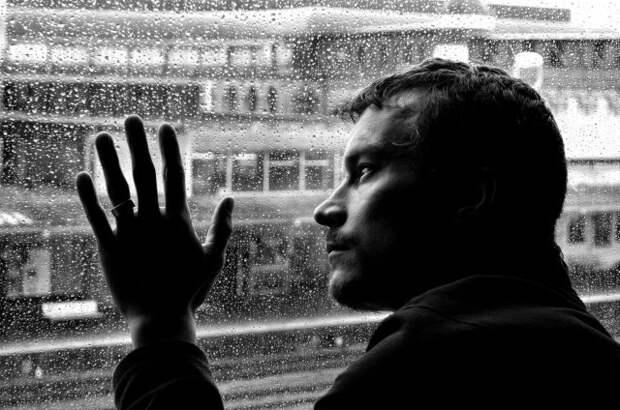 черно-белое фото мужчины, смотрящего в окно