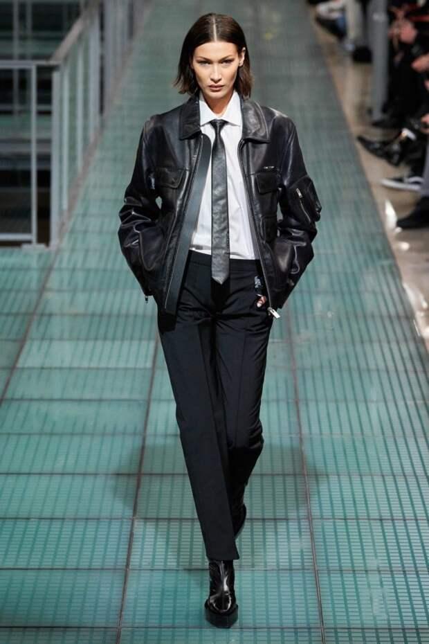 модель на подиуме в кожаной куртке и галстуке