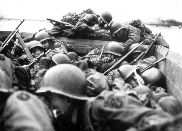 Американские солдаты на десантной лодке форсируют Рейн под огнем немецких солдат.