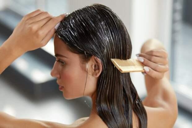 девушка брюнетка расчесывает волосы с кондиционером