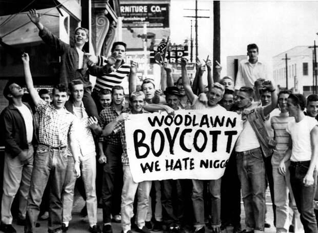 Большая группа белых американских школьников с самодельным плакатом Бойкот. Мы ненавидим негров